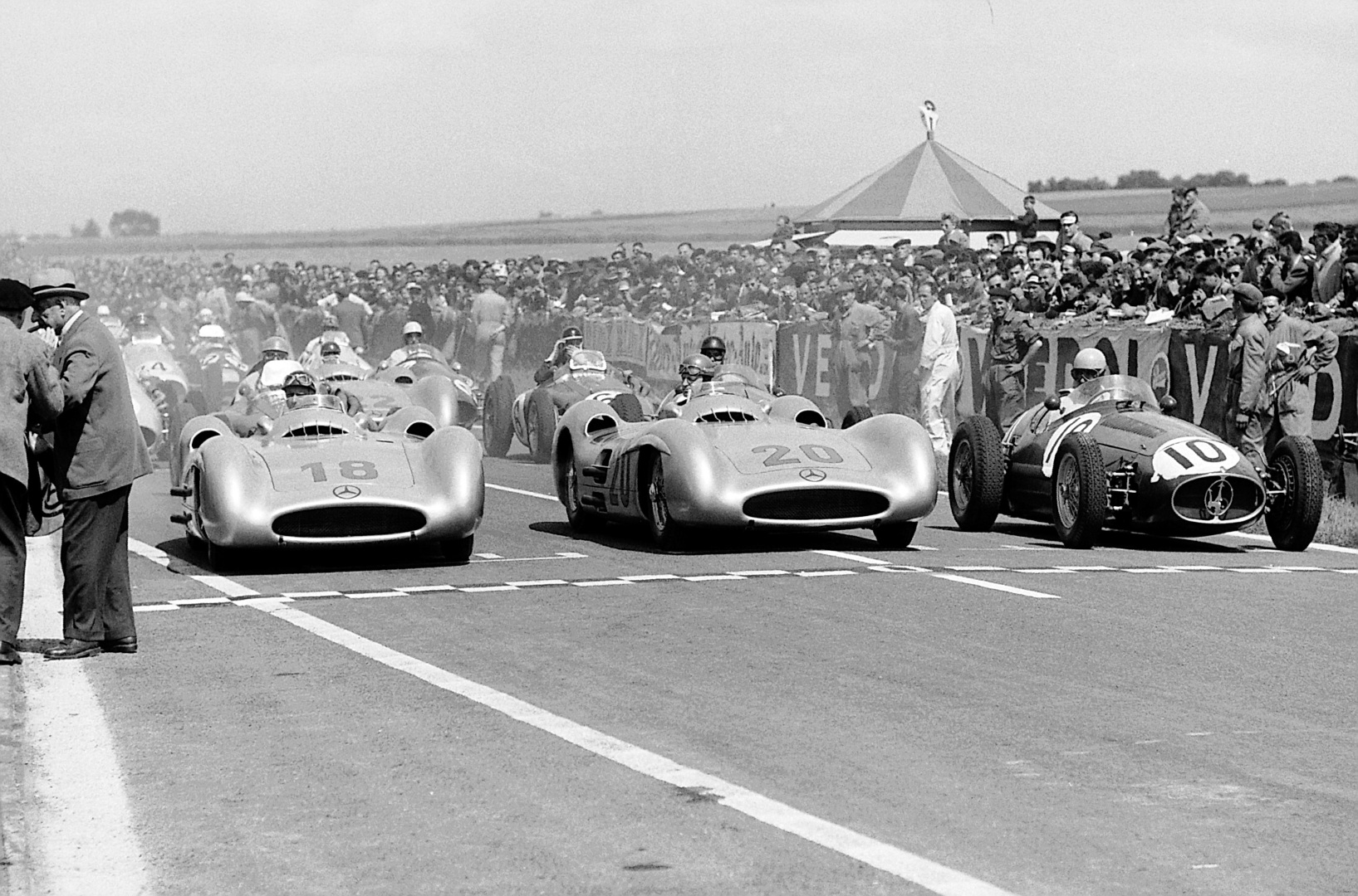 Double victory in the French Grand Prix in Reims, July 4, 1954. Lining up in the first row before the start: Juan Manuel Fangio (start number 18), the winner of the race, Karl Kling (start number 20) who finished in second place, both driving Mercedes-Benz W 196 R Formula One racing cars, and Alberto Ascari (start number 10) at the wheel of a Maserati 250 F.